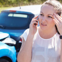 woman on the phone after getting into an accident